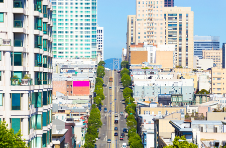 bay bridge: Distant telephoto view down California Street of iconic cable car and tip of Bay Bridge among residential apartment buildings on clear sunny day in San Francisco. Horizontal Editorial