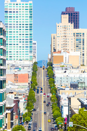 bay bridge: Distant telephoto view down California Street of iconic cable car and tip of Bay Bridge among residential apartment buildings on clear sunny day in San Francisco. Vertical