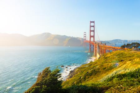 Zonlicht zorgt voor een hoge belangrijkste hoogtepunten, lens flare op Marin Headlands met Golden Gate Bridge gezien over rotsachtige kustlijn bij Fort Point tijdens zonsondergang in San Francisco, Californië. Horizontale kopiëren ruimte