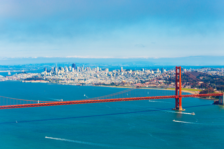 High angle, mid-air, aerial view of downtown San Francisco city, bay seen together with Golden Gate Bridge on a summer, blue sky day in California, compressed using telephoto lens