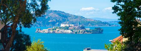 lejos: Amplia vista panorámica de teleobjetivo Alcatraz Penitenciario Federal y la isla en medio de la bahía de San Francisco enmarcada por los árboles desde el ángulo alto en un día soleado en California