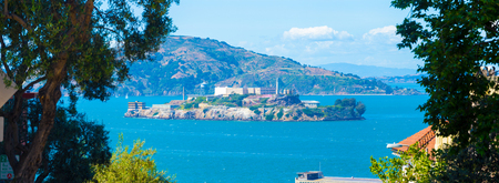 Wide panoramic telephoto view of Alcatraz Federal Penitentiary and island in middle of San Francisco bay framed by trees from high angle on sunny day in California