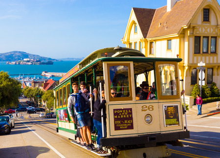 san: San Francisco, USA - May 12, 2016: Closeup of approaching Hyde Street cable car full of people standing on outside platform enjoying steep hill ride with Alcatraz Island background
