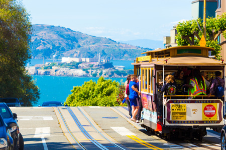San Francisco, USA - May 15, 2016: Telephoto compressed view of Alcatraz Island and cable car full of tourist passengers at crest of Hyde Street on sunny day