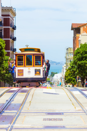 san: San Francisco, USA - May 19, 2016: Oncoming cable car is full of outside hanging and platform standing tourists with bay water background in sunny Powell Street in California. Vertical