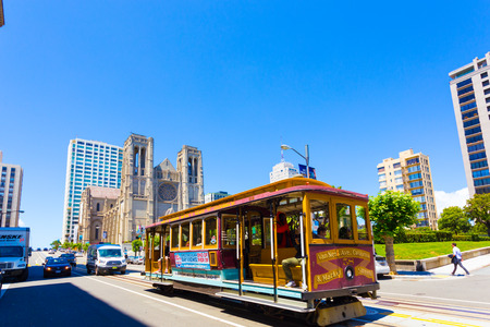 San Francisco, USA - May 20, 2016: Cable car rolls down California Street in front of Grace Cathedral on top of Nob Hill. Horizontal with wide angle distortion
