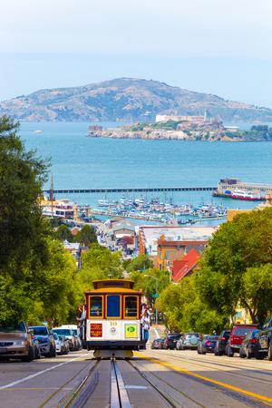 샌프란시스코, 미국 -2006 년 5 월 19 일 : 천사와 알 카트 라 즈 섬, 맑은 캘리포니아에서 하이드 스트리트에 백그라운드에서 베이 물 오르막 오는 관광객