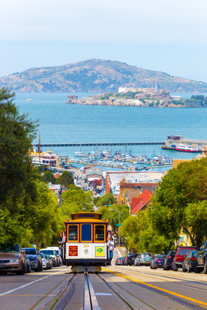 San Francisco, USA - May 19, 2016: Approaching cable car full of tourists coming uphill with Angel and Alcatraz Island, bay water in background on Hyde Street in sunny California Editoriali
