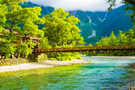 Man crossing Kappa-bashi Bridge with Mount Hotaka background during early sunny morning in the Japanese Alps in Kamikochi, Nagano Prefecture, Japan. Horizontal Banque d'images