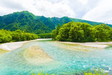 Mountains and crystal clear Azusa River in this pristine and untouched nature landscape in Japanese Alps town of Kamikochi, Nagano Prefecture, Japan. Horizontal