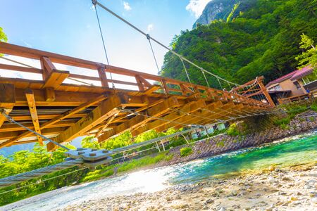 Low angle view from underneath Kappa-Bashi Bridge over the clear water of the Azusa River with mountains and sky background at morning in Kamikochi, Nagano Prefecture, Japan. Horizontal Stock Photo