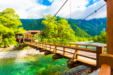 View of Mount Hotaka behind rustic Kappa Bashi Bridge over clear turquoise water of Azusa River in pristine Japanese Alps village of Kamikochi, Nagano Prefecture, Japan