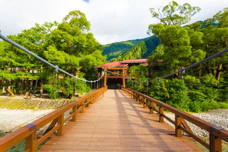 La cubierta de madera centrada del puente de Kappa Bashi que lleva a los hoteles aislados en la luz de la madrugada en la ciudad japonesa de los alpes de Kamikochi, Nagano, Japón. Horizontal