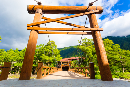 Low angle view of large wooden posts marking the entrance to Kappa Bashi Bridge in Japanese Alps tourist village of Kamikochi, Nagano Prefecture, Japan Stock Photo