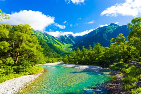 The pristine alpine water of Azusa River flowing in front of landscape view of Mount Hotaka-Dake on a sunny, blue sky day in Japanese Alps village of Kamikochi, Nagano, Japan. Horizontal