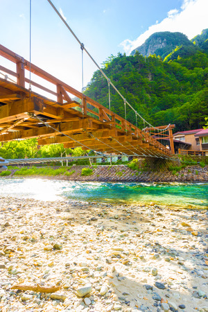 Low angle view from underneath Kappa Bashi Bridge over the clear water of the Azusa River with mountains and sky background at morning in Kamikochi, Nagano Prefecture, Japan. Vertical Stock Photo