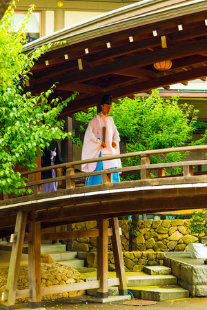 shinto: Tokyo, Japan - June 25, 2016: Shinto priest in traditional kannushi robe walking across atmospheric wooden bridge at Yushima Tenmangu shrine