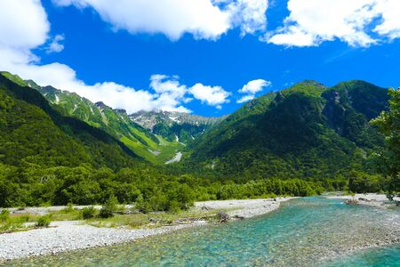 Pristine, crystal clear Azusa river flowing below snow capped Hotaka Dake Mountain in Japanese alps village of Kamikochi, Nagano, Japan. Horizontal