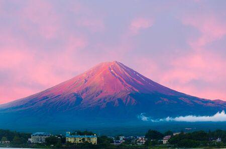 kawaguchi ko: Fiery colorful sky above the red crater cone of Mount Fuji at dawn sunrise over Lake Kawaguchiko water on a summer morning in Japan Stock Photo