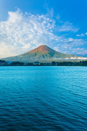 kawaguchi ko: Centered Mount Fuji bathes in morning side light while Lake Kawaguchiko sits in shadow below cloudy blue sky on a summer day in five lakes region of Japan. Vertical Stock Photo
