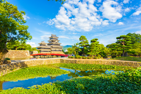 lilypad: Small pond containing lily pads in the foreground of the ancient keep of Matsumoto Jo Castle on a summer day with clouds in Nagano Prefecture, Japan. Horizontal