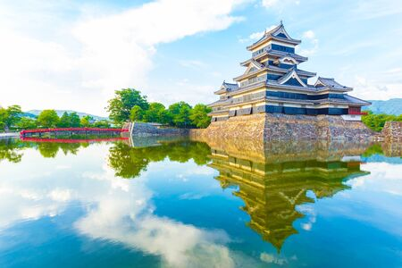 sky reflection: A soft evening light on the keep of Matsumoto Castle and sky as moat water reflection shows mirror image in Nagano Prefecture, Japan