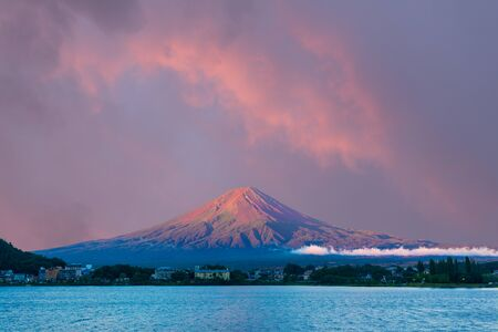 kawaguchi ko: Colorful pink sunrise sky above the bright red volcanic cone of Mount Fuji with line of lake shore hotels in foreground during summer morning at Kawaguchiko, Japan. Copy space