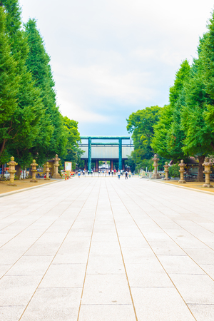 Tokyo, Japan - July 30, 2015: Daini Torii gate in the distance on tree lined path at entrance to controversial Yasukuni Shinto Shrine on a gloomy overcast day