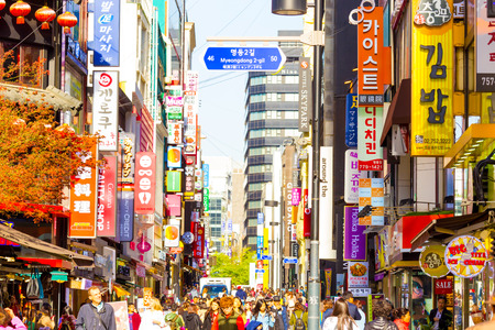 Seoul, South Korea - April 17, 2015: People walking down bustling Myeongdong pedestrian shopping street surrounded by commercialism of stores, signs and crowded with tourists. Horizontal 에디토리얼