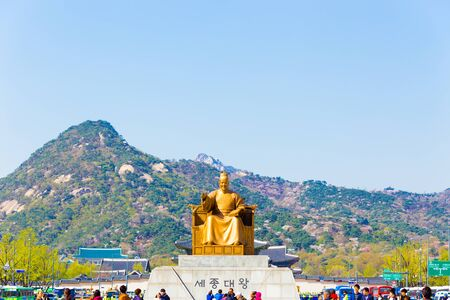 Seoul, South Korea - April 17, 2015: Tourists walking around centered King Sae Jong Dae Wang statue in front of Bugaksan mountain in city center, downtown on a blue sky day Editorial