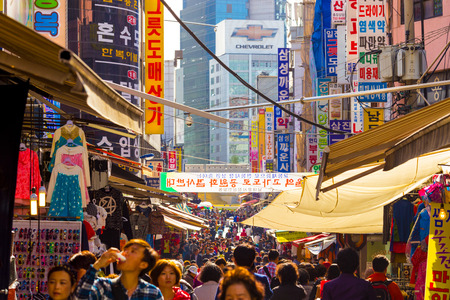 Seoul, South Korea - April 17, 2015: People walking down bustling Namdaemun Market pedestrian shopping street surrounded by stores, signs and crowded with shoppers. Horizontal