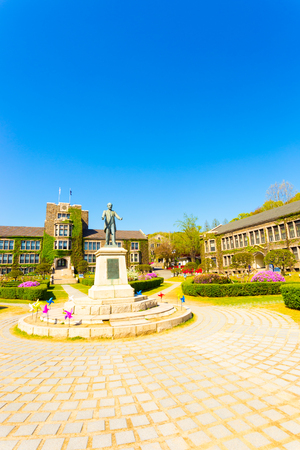 Ivy covered brick buildings surround the quad with Horace Grant Underwood statue at venerable Yonsei University in Sinchon, Seoul, South Korea. Vertical Stock Photo
