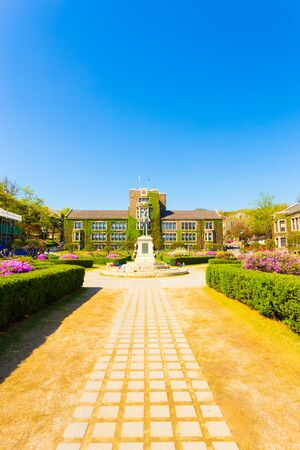 underwood: Path leading to Horace Grant Underwood statue surrounded by ivy covered buildings on main quad of Sinchon campus of Yonsei University in Seoul, South Korea