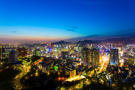 night dusk: Colorful sunset behind high angle view of downtown Seoul cityscape with commercial buildings and mountains in horizon at dusk on a clear sky spring night in South Korea
