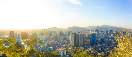 Dramatic high key backlight behind panoramic aerial view of downtown Seoul cityscape with commercial buildings and mountains in horizon background on a lovely spring day in South Korea Stok Fotoğraf