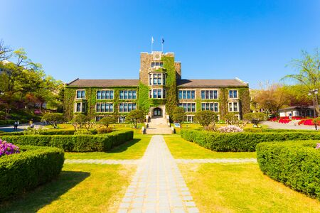 Grassy walking path leading to ivy covered main building at venerable Yonsei University in Sinchon, Seoul, South Korea. Horizontal Stock Photo