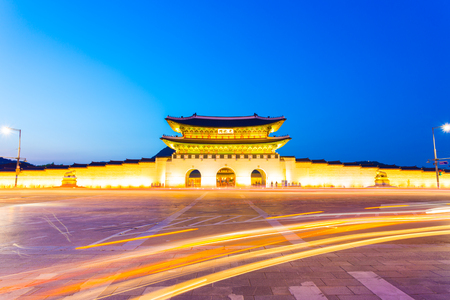 night dusk: Long exposure car lights curving in front of Gwanghwamun main entrance gate to Gyeongbokgung Palace in historic part of downtown Seoul, South Korea on a clear, dusk night