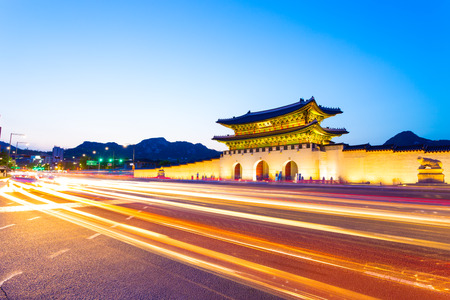 main gate: Colorful streaking headlights of cars passing in front of lighted gate of Gwanghuamun, entrance to historic Gyeongbokgung Palace at twilight in downtown Seoul, South Korea. Horizontal Stock Photo