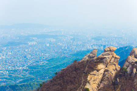 valley below: View of Seoul cityscape from peak of Bukhansan mountain where smog and air pollution prevents clear view buildings in valley below Stock Photo