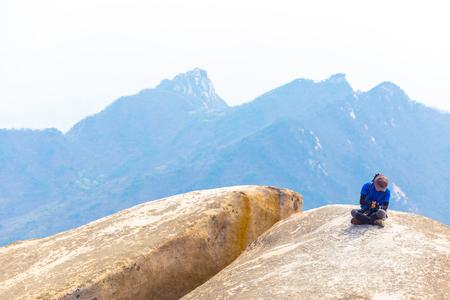 Seoul, South Korea - April 23, 2015: Korean man decked out in colorful trekking fashions resting on boulder atop Baegundae Peak after hiking Bukhansan mountain