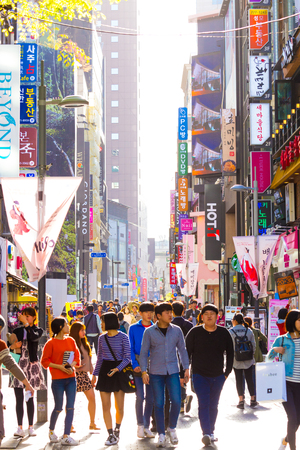 Seoul, South Korea - April 17, 2015: Young Koreans walking down busy backlit Myeongdong pedestrian shopping street with commercialism of many store signs and crowded with shoppers