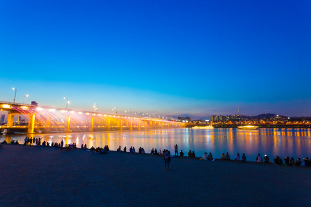 night dusk: People watching Moonlight Rainbow water fountain and colorful light show from Banpo Bridge over the Han River at dusk on a clear night in Gangnam, Seoul, South Korea. Horizontal Stock Photo