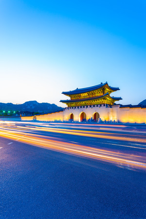 streaking: Colorful streaking car lights passing in front of lighted gate of Gwanghuamun, entrance to historic Gyeongbokgung Palace at twilight in downtown Seoul, South Korea. Vertical