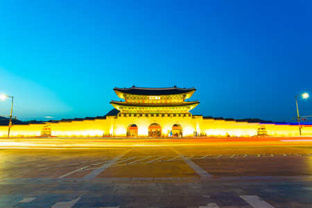 main gate: Long exposure car lights leaving a straight light trail in front of Gwanghwamun main entrance gate to Gyeongbokgung Palace in historic part of downtown on a clear, twilight night in Seoul, South Korea