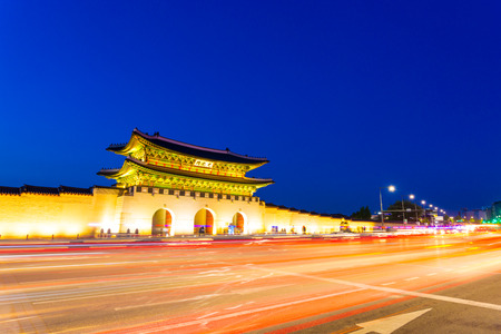 main gate: Long exposure streaking car tail lights leaving trailing light in front of Gwanghwamun main gate to Gyeongbokgung Palace at dusk in downtown on a clear night in Seoul, South Korea Editorial