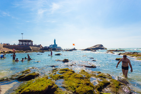 southernmost: Kanyakumari, India - February 22, 2015: Indian tourists swimming in shallow rocky beach with Thiruvalluvar statue and 16 legged mandap pavilion in background Editorial
