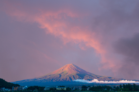 Beautiful red sunrise sky above the bright red volcanic cone of Mount Fuji with line of lake shore hotels in foreground during summer morning at Kawaguchiko, Japan. Copy space