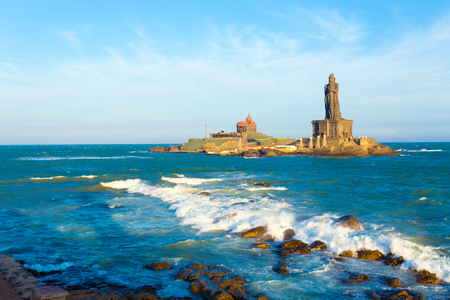 neighboring: Vivekananda Rock is home to a memorial and neighboring island Thiruvalluvar Statue off the coast of Kanyakumari, Tamil Nadu, India on a blue sky day. Horizontal
