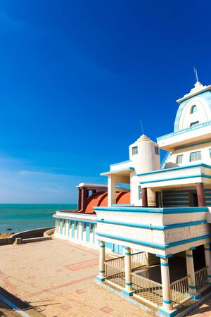 Side oceanfront view of Gandhi Memorial Mandapam on the Indian southernmost tip city of Kanyakumari on a sunny, blue sky day in Tamil Nadu, India. Vertical