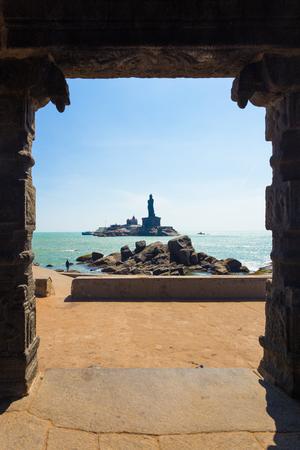 southernmost: The Thiruvalluvar statue island seen through the 16 legged mandap pavilion on a blue sky day in Kanyakumari, Tamil Nadu, India